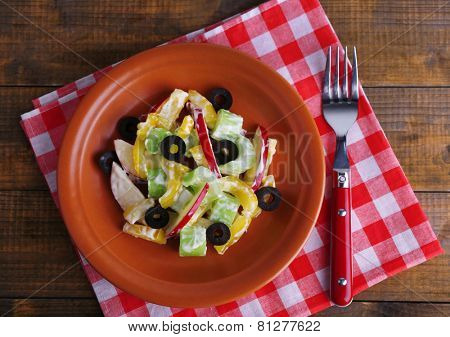 Waldorf salad with olive on plate on table close up
