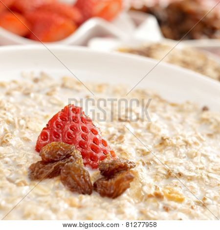 closeup of a bowl with porridge with sultana raisins and strawberry