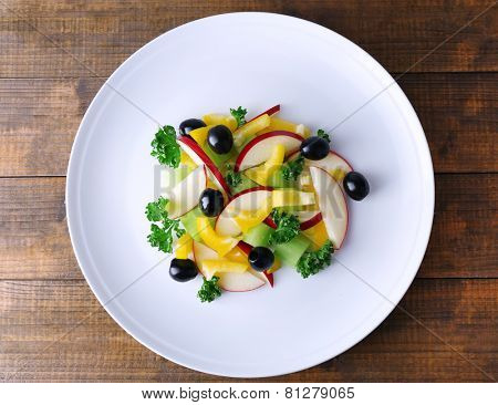 Waldorf salad with olive on plate on wooden background