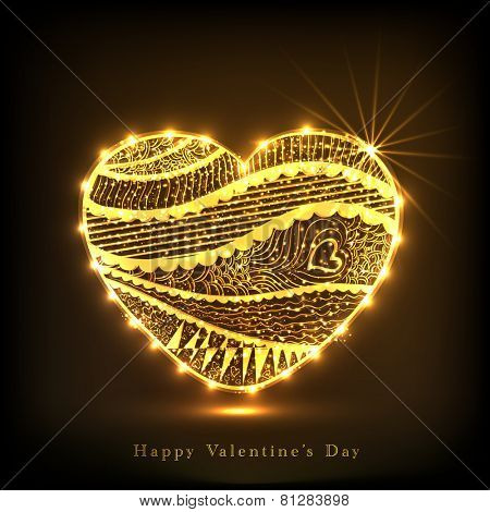 Shiny golden heart decorated with floral design on brown background for Happy Valentines Day celebration.