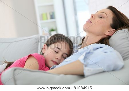 Mother and daughter taking a nap on couch