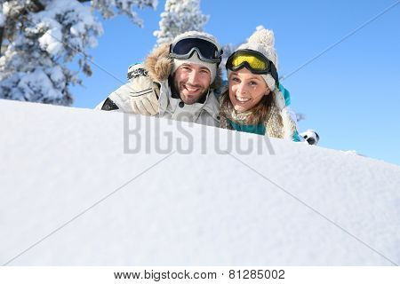 Cheerful couple of skiers laying down in snow