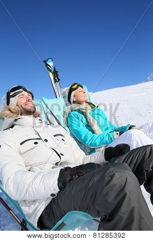 Couple of skiers sunbathing at top of ski slope