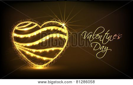 Shiny golden heart on brown background for Happy Valentines Day celebration.