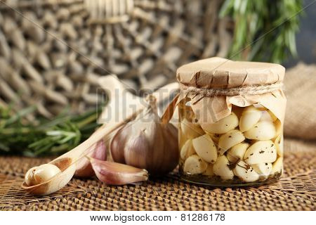 Canned garlic in glass jar and wicker mat and rosemary branches, on wicker mat background