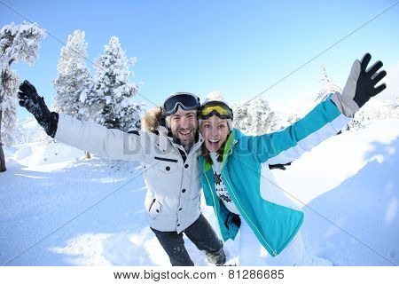 Cheerful couple of skiers lifting arms up