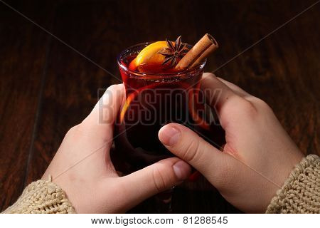 Man's Hands Hold A Glass With Mulled Wine, Mulled Wine With An Orange, Honey, Cinnamon, A Carnation