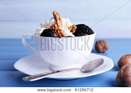 Dessert with prunes and nuts in cup on color wooden table background