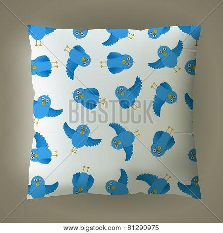 Pillow with blue bird pattern.