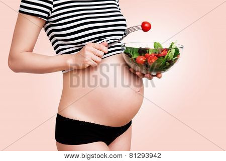 Pregnant woman with a bowl of vegetables