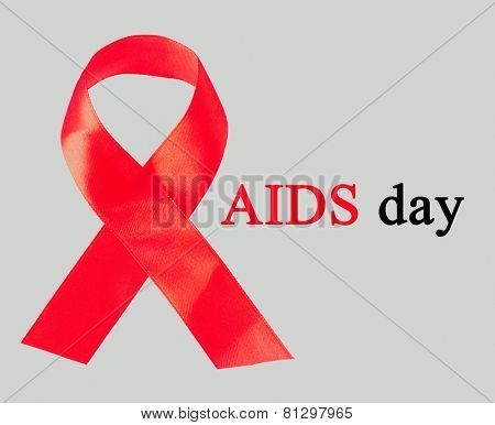 Red AIDS ribbon on grey background