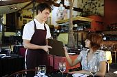 stock photo of waiter  - waiter giving menu to female costumer at the restaurant - JPG