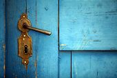 image of door-handle  - Color shot of a vintage door handle on a wooden blue door.