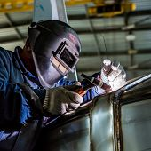 stock photo of engineering construction  - Man welding with reflection of sparks on visor - JPG