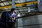picture of manufacturing  - Man welding with reflection of sparks on visor - JPG