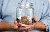stock photo of holding money  - Man holds a glass jar containing United States coins and money - JPG