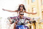 pic of vespa  - Beautiful young couple riding scooter together while happy woman keeping arms outstretched and smiling - JPG