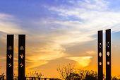 foto of sundial  - Soft sunset framed by sundial posts at neighborhood park - JPG
