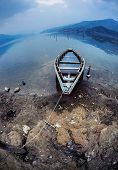 stock photo of flood  - Wooden flooded boat on the shore of Fewa Tal at overcast blue sky in Pokhara Nepal - JPG