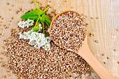 pic of buckwheat  - Buckwheat with a flower buckwheat and a spoon on a wooden boards background - JPG