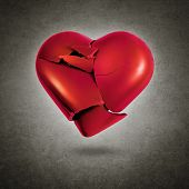 image of broken hearted  - Broken red heart hovering over a gray textured background - JPG