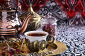 stock photo of bud  - Tea in a beautiful metal Cup with Oriental motifs on the metal tray surrounded by dried rose buds - JPG