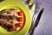 foto of pangasius  - Dish of Pangasius fillet with rosemary and cherry tomatoes in plate on color wooden table background - JPG