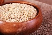 pic of sackcloth  - Brown rice in bowl on sackcloth background - JPG