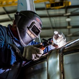stock photo of welding  - Man welding with reflection of sparks on visor - JPG