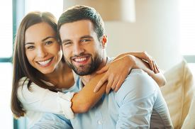 stock photo of candid  - Beautiful young loving couple sitting together on the couch while woman embracing her boyfriend and smiling  - JPG