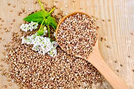 foto of buckwheat  - Buckwheat with a flower buckwheat and a spoon on a wooden boards background - JPG