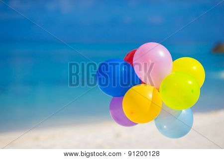 Multicolored balloons on white tropical beach