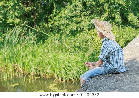 Teenager with wooden rustic fishing rod angling on concrete bridge