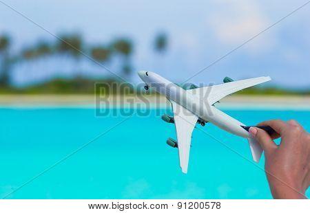 Small white miniature of an airplane on beach