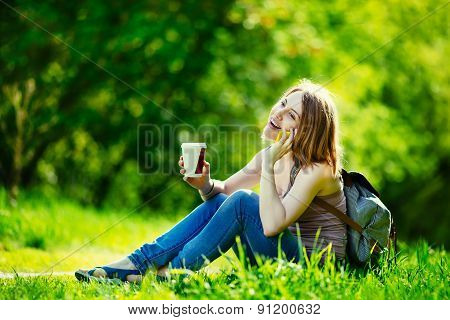 Attractive young woman talking by phone and holding cup of coffee outdoors
