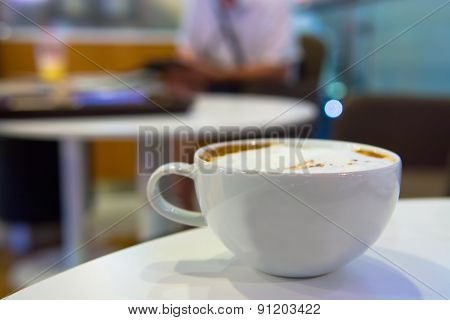 Cappuccino or latte coffee in white cup on desk