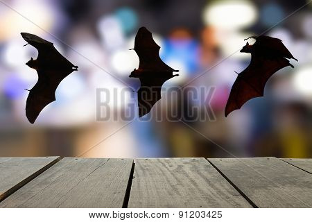 Terrace Wood And Bats Flying In Sky With Bokeh Of City Lighting