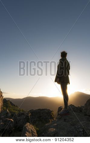 Girl watching sunset at the top of the mountain. Vertical