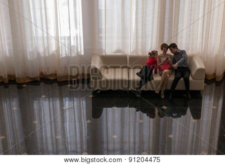 Family Sitting And Using A Mobile Phone