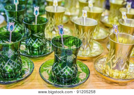 Background of many cups for Turkish tea from green and yellow glass in the bazaar in Istanbul