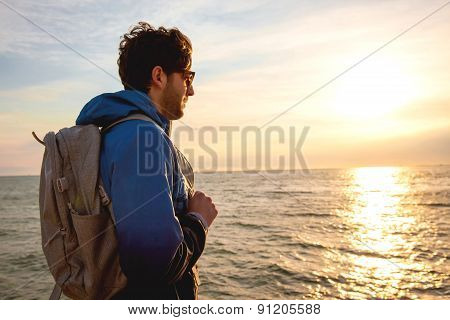 Young Man Wearing A Backpack Standing By The Sea