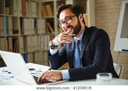 Elegant businessman in eyeglasses networking in office