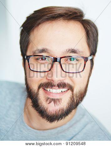Happy young man with beard looking at camera