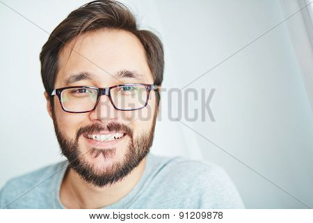 Happy young man in eyeglasses looking at camera with toothy smile