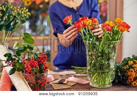 Female florist working with fresh flowers in design studio