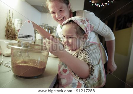 Mother Smiling And Tutoring Her Daughter In The Kitchen