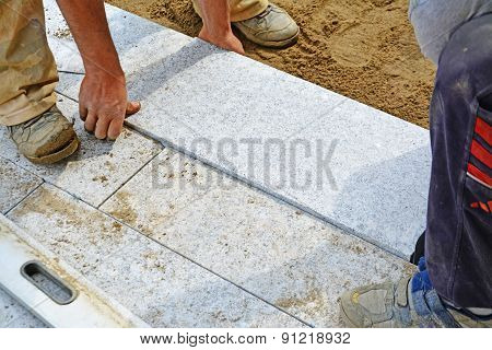 Workers Laying Granite Block Paver In Place