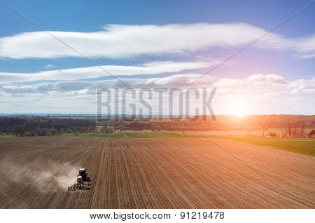 Aerial View Of The Sunset Above The Tractor Harrowing The Field