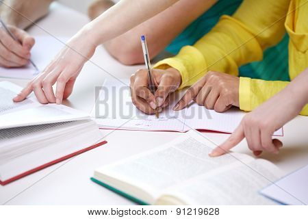 education, people and school concept - close up of students hands with textbooks writing to notebooks at school