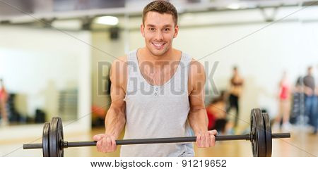fitness, sport, training, gym and lifestyle concept - smiling man with barbell in gym